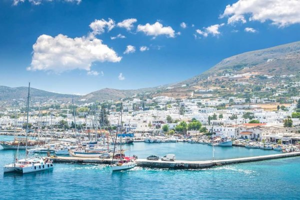 Beautiful view of Parikia town in Paros island, Greece, Islands. There are white houses and boats in the old harbor.